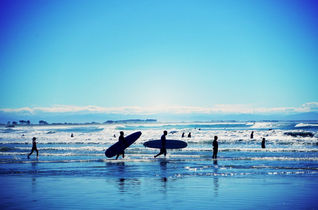 surfers on the beach in New Zealand